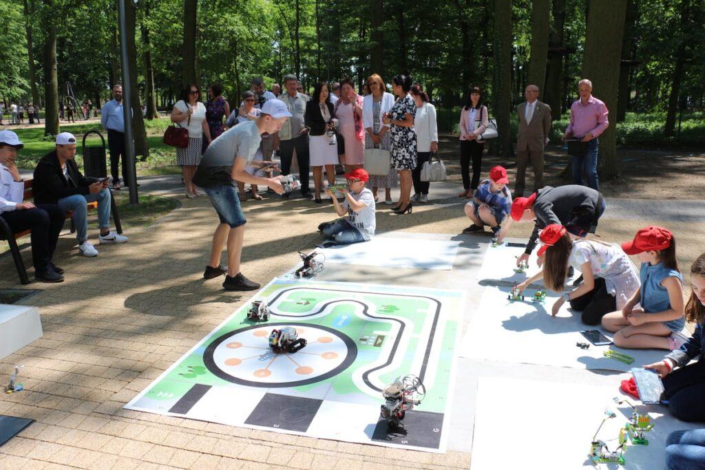 Na pierwszym planie dzieci wykonujące roboty z klocków w parku fizyki. W tle obserwujący ich zmagania dorośli.