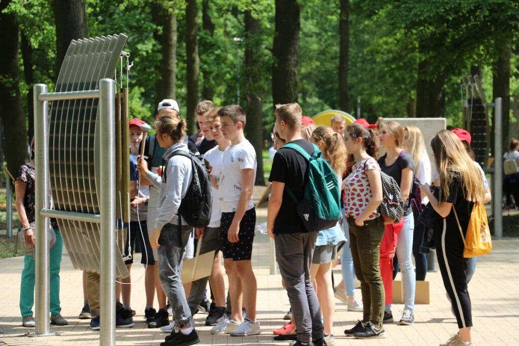 Grupa dzieci w późno-szkolnym zgromadzona wokół jednej z atrakcji parku fizyki