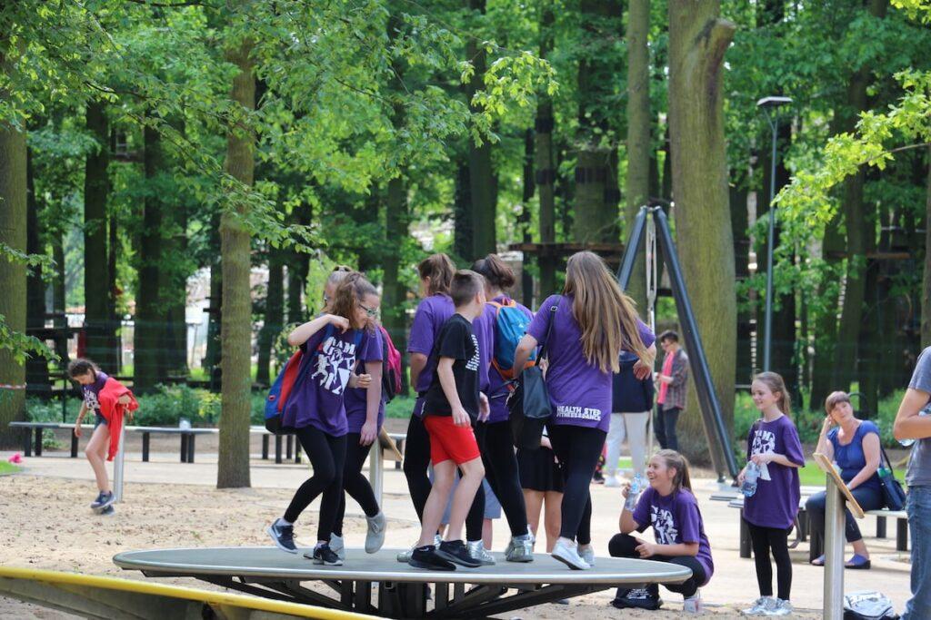 Grupa dzieci w wieku szkolnym korzysta z jednej z atrakcji w parku fizyki