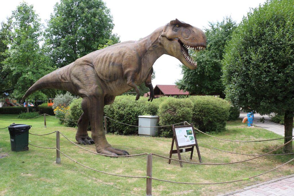 Figura Tyranozaura stojącego na trawie w w parku
