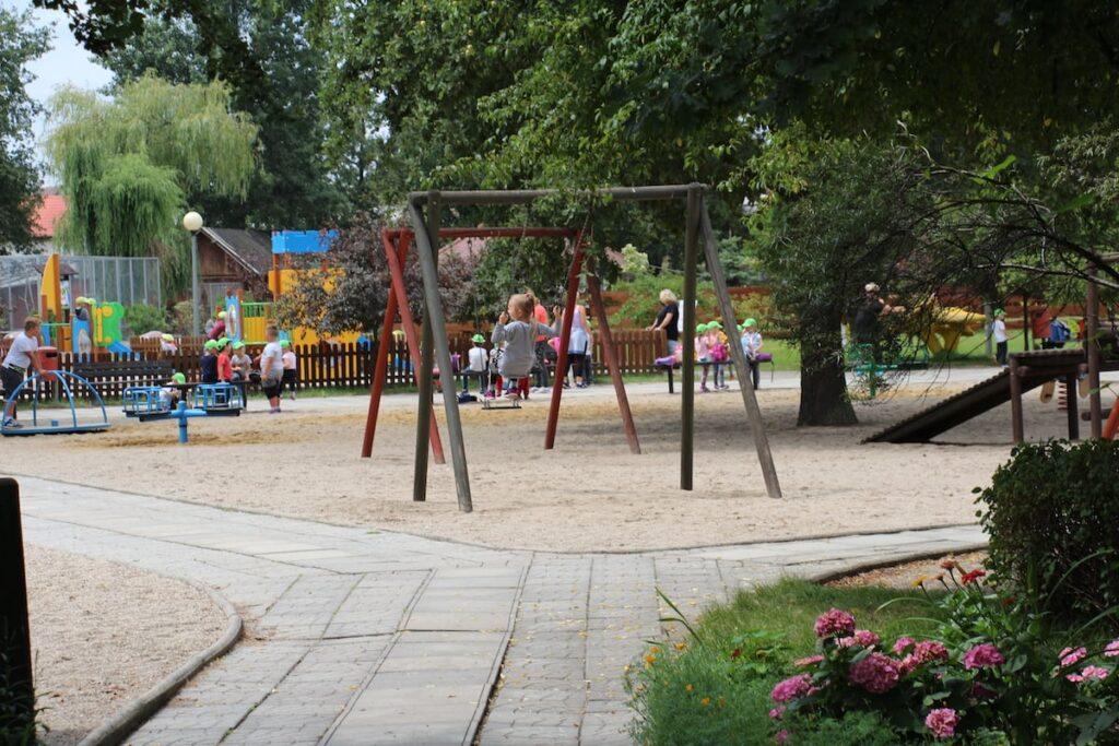 Widok z parkowej ścieżki na plac zabaw. Na pierwszym planie huśtawka, w tle bawią się dzieci.
