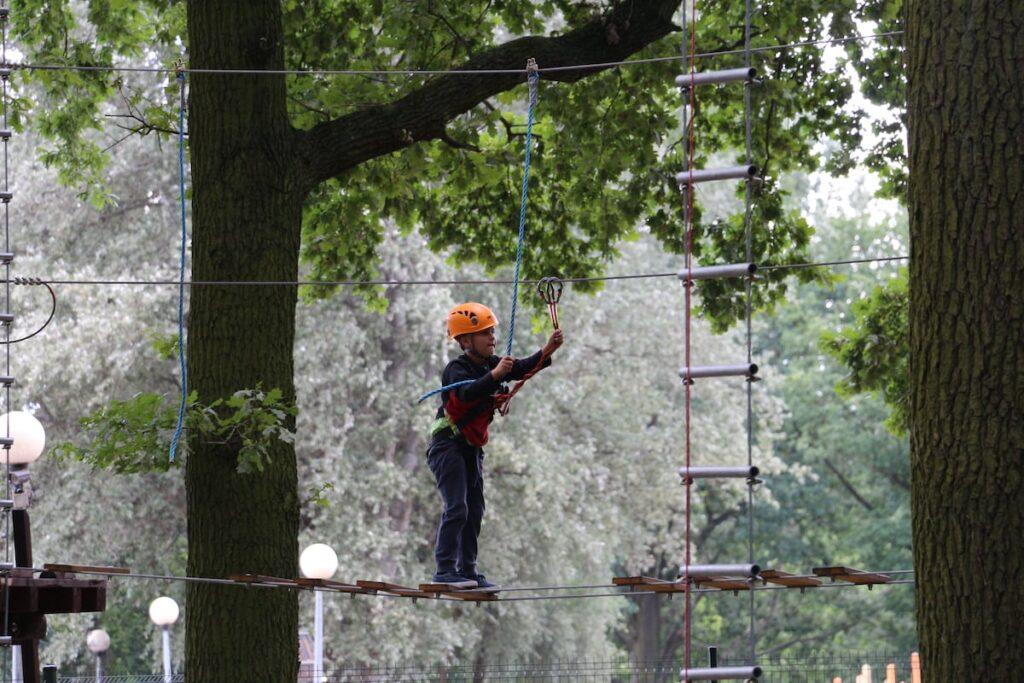 Dziecko pokonujące przeszkodę w parku linowym