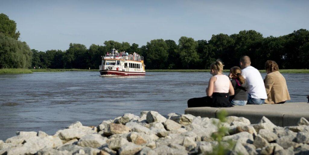 Siedząca na kamiennym brzegu rupa osób (na pierwszym planie) obserwuje nadpływający statek wycieczkowy