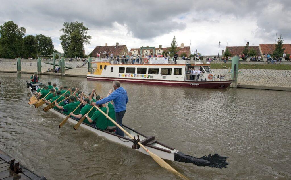 Kilkunastoosobowa grupa wioślarzy przepływa obok statku wycieczkowego