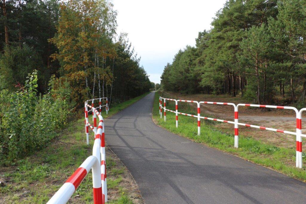 Zakręt na ścieżce rowerowej biegnącej przez las. Po bokach barierki.