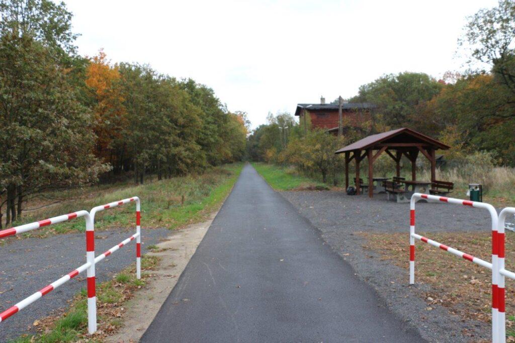 Asfaltowa ścieżka rowerowa tuż przed wjazdem do lasu. Po prawej zadaszone miejsce na odpoczynek.