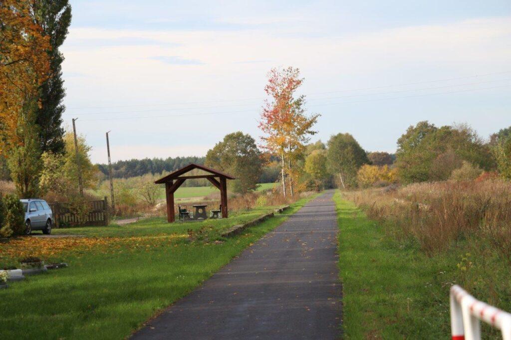 Ścieżka rowerowa przebiegająca przez polanę. W oddali, na poboczu zadaszone miejsce na odpoczynek.