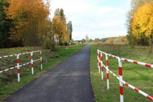Ścieżka rowerowa biegnąca przez polanę. Po bokach biało-czerwone barierki.
