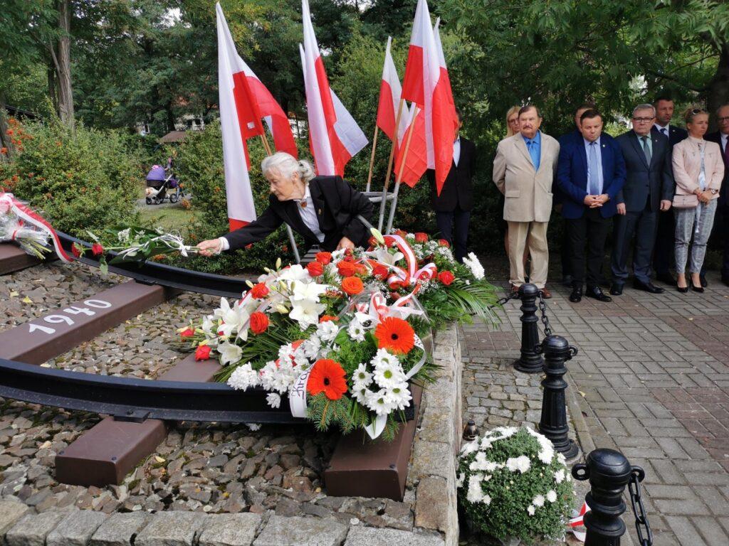 Danuta Cygan składa kwiaty przed pomnikiem Sybiraka. W tle pozostali uczestnicy uroczystości