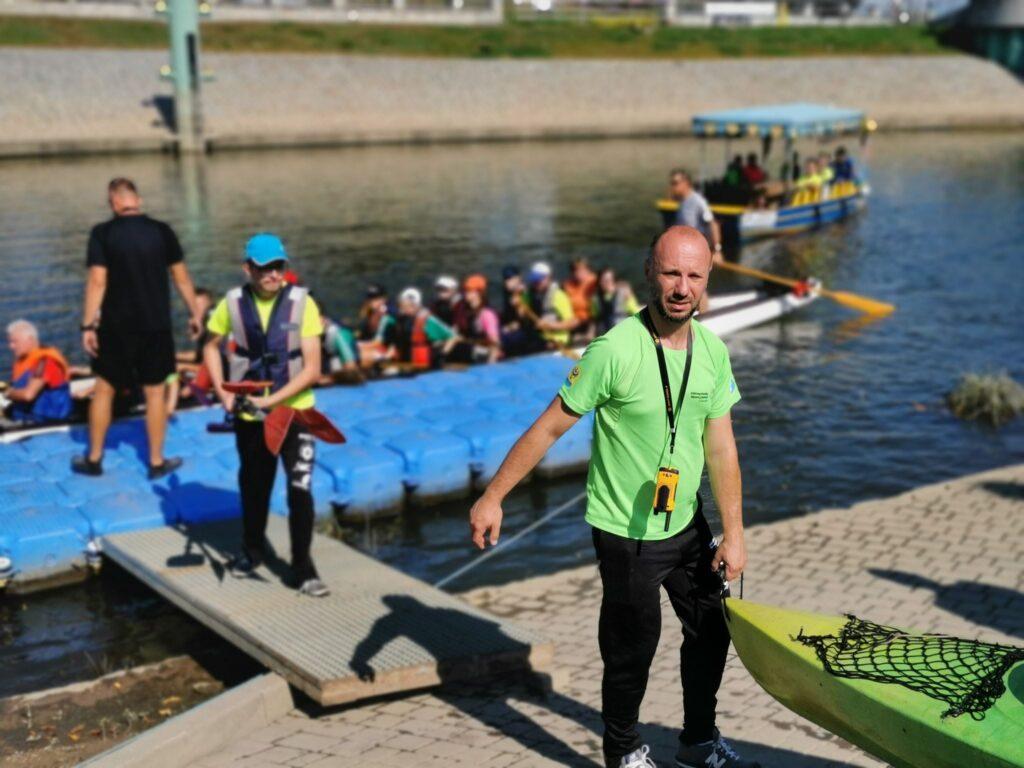 Na zdjęciu widzimy jednego z organizatorów spływu wynoszącego na brzeg rzeki swój kajak
