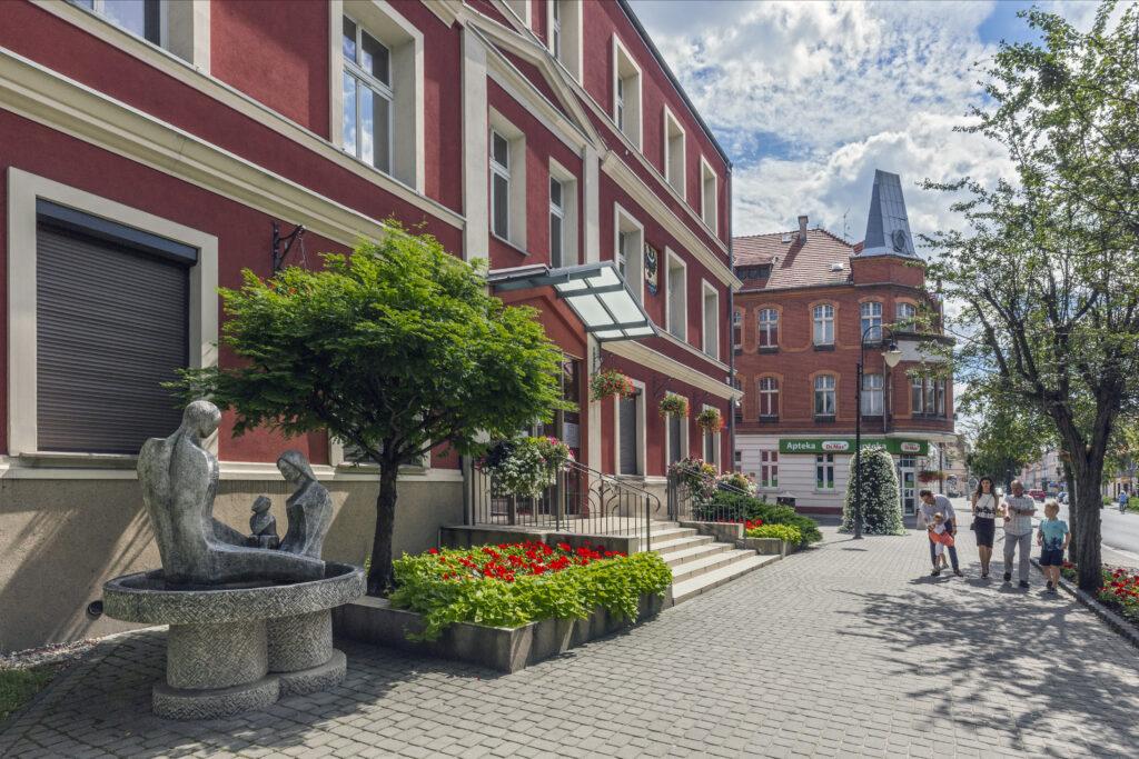 Na zdjęciu znajduje się budynek Urzędu Miejskiego w Nowej Soli przy ulicy Piłsudskiego 12. W tle mieszkańcy.