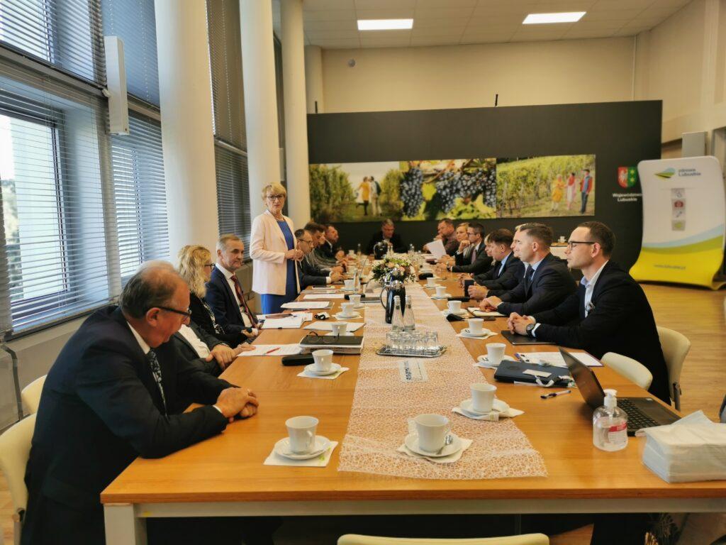Na zdjęciu przedstawiciele lubuskich samorządowców na spotkaniu z marszałek województwa Elżbietą Polak. Marszałek Polak przemawia do zgromadzonych wokół stołu zebranych gości.