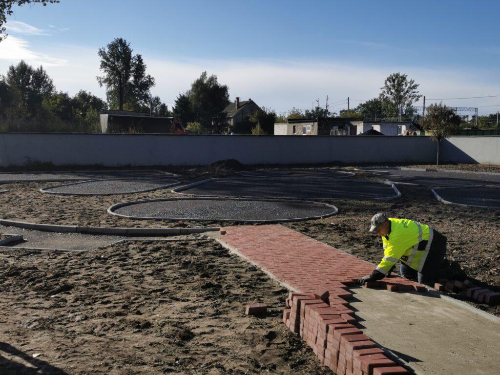 Na obrazku podbudowa pod przyszły plac zabaw przy SP2 na pierwszym planie pracownik układający chodnik z kostki brukowej