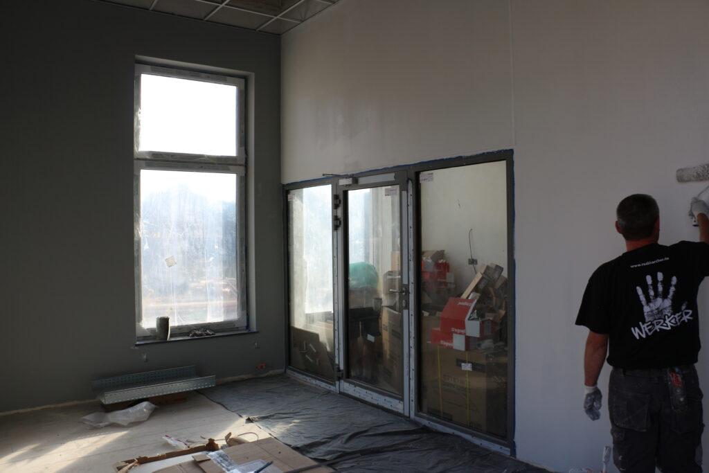 Na zdjęciu mężczyzna stojący tyłem, malujący ścianę w budyznku wieży zegarowej