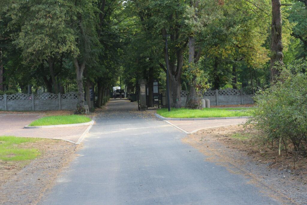 Asfaltowa droga do cmentarza przy ulicy Piaskowej w Nowej Soli w tle drzewa oraz brama wjazdowa