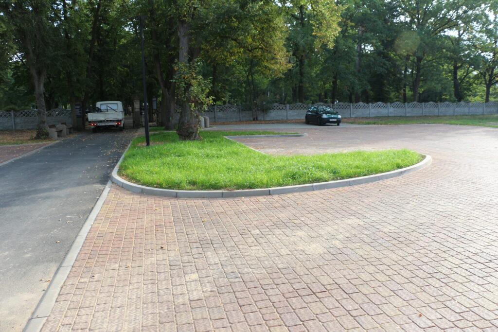 Parkingi przed wjazdem na cmentarz przy ulicy Piaskowej. W tle samochody oraz drzewa