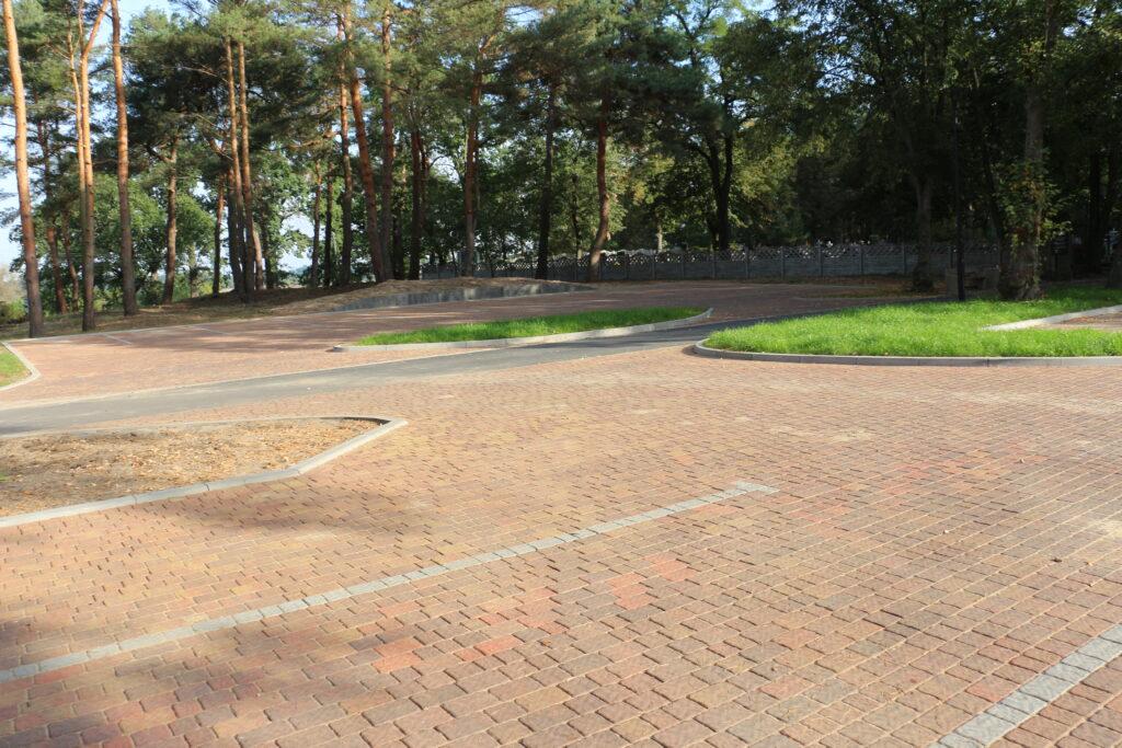 Parkingi przed wjazdem na cmentarz przy ulicy Piaskowej. W tle ogrodzenie cmentarza oraz drzewa