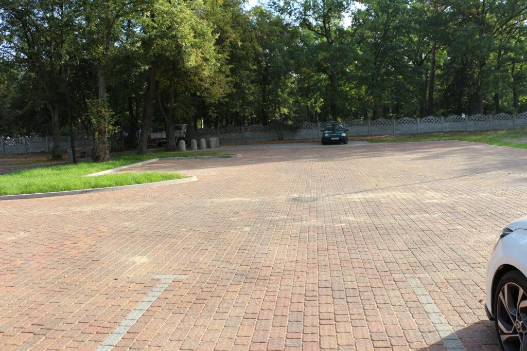 Parkingi przed wjazdem na cmentarz przy ulicy Piaskowej. W tle ogrodzenie cmentarza oraz zaparkowane samochody
