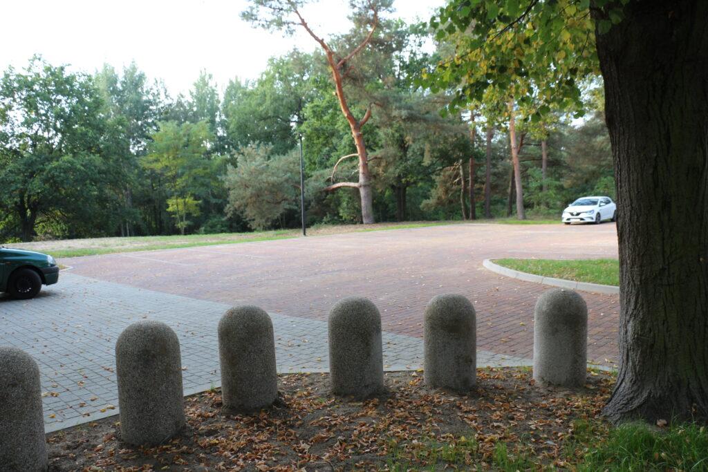 Parkingi przed wjazdem na cmentarz przy ulicy Piaskowej, na pierwszym planie kamienne słupki oddzielające część parkingów od drogi
