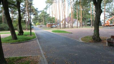 Widok na drogę doprowadzającą do cmentarza przy ulicy Piaskowej. Po obu stronach drogi parkingi przy których rosną drzewa. W tle domy i samochody