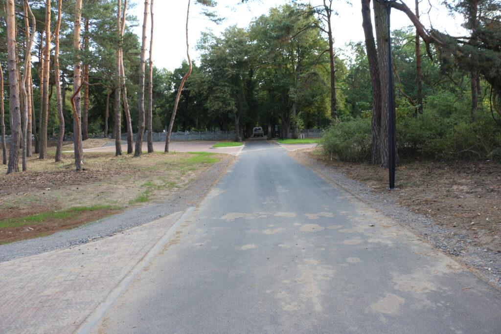 droga do cmentarza przy ulicy Piaskowej, po ubu stronach jezdni drzewa, w tle brama wjazdowa do cmentarza oraz jego ogrodzenie