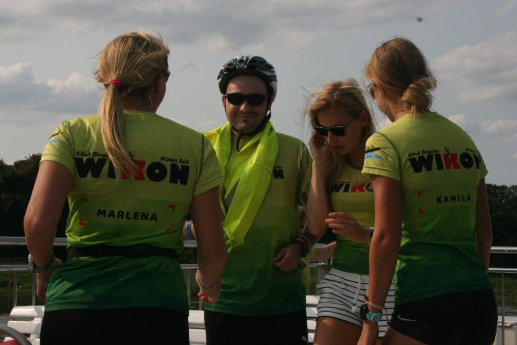 Na zdjęciu znajdują się uczestnicy rejsu laguną po Odrze: trzy kobiety i jeden mężczyzna. Mężczyzna jest w kasku rowerowym.