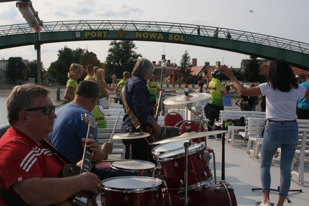 Na zdjęciu znajduje się widok na górny pokład statku Laguną. Na pierwszym planie widać muzyków, za nimi uczestnicy rejsu.