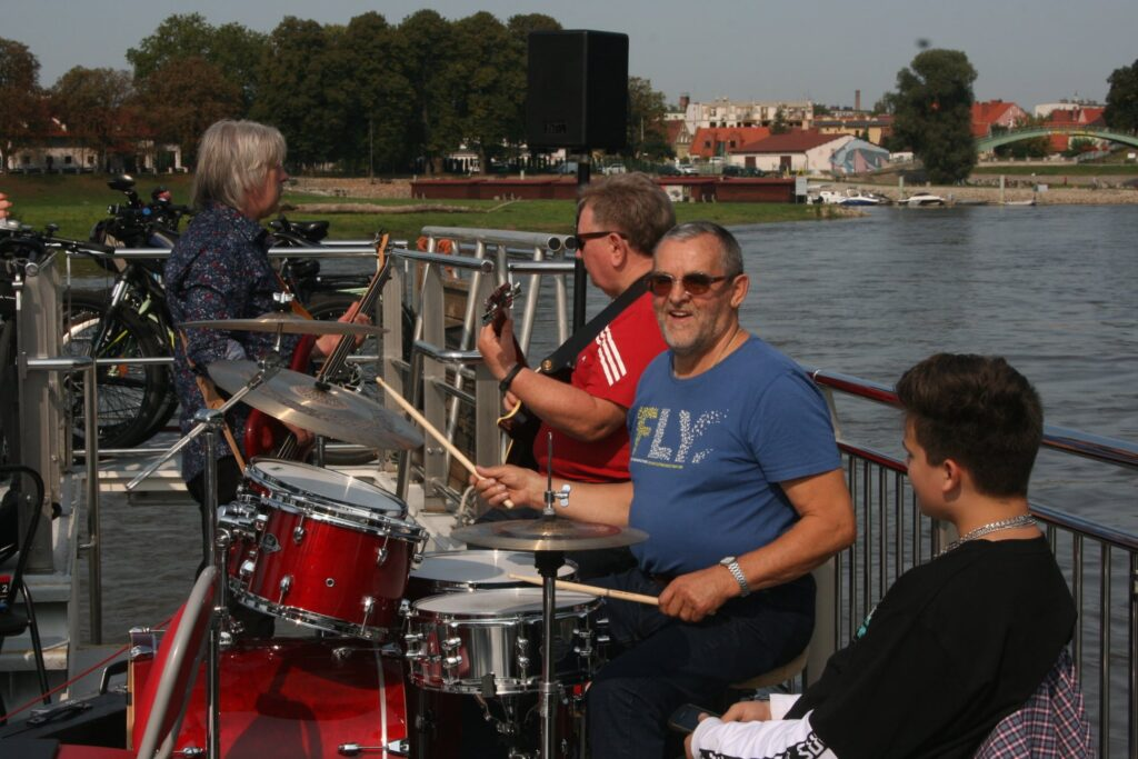 Na zdjęciu znajdują się muzycy uczestniczący w rejsie laguną. Na pierwszym planie perkusista, za nim dwóch gitarzystów