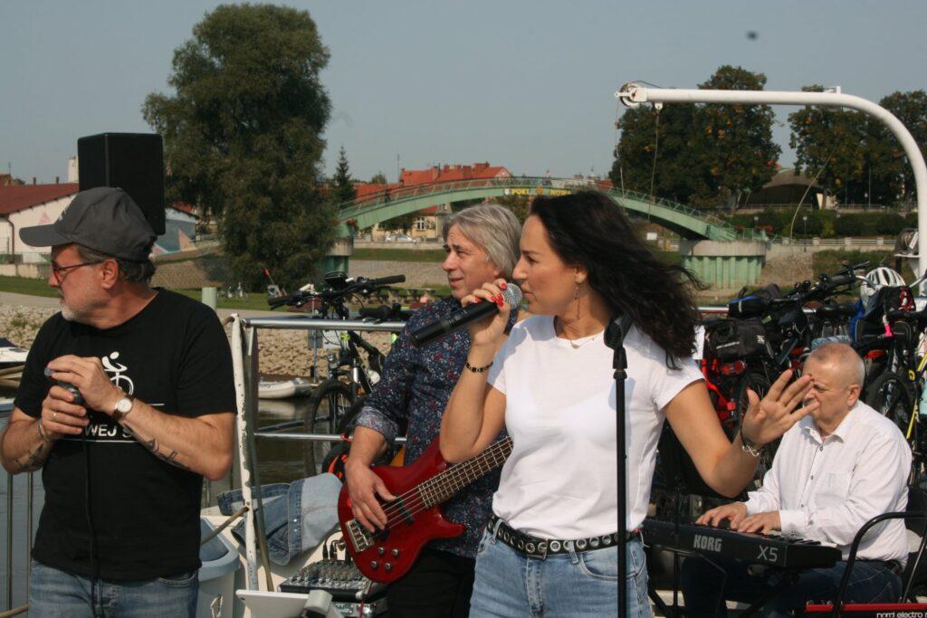 Na zdjęciu po lewej stronie znajduje się Tadeusz Szechowski który gra na ustnej harmonijce. Obok niego wokalistka Justyna Sokołowska, w tle pozostali muzycy