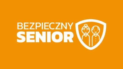 Logo programu Bezpieczny Senior, biały napis na pomarańczowym tle, na tarczy widnieje wizerunek dwóch starszych osób - kobiety i mężczyzny.