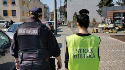 Na zdjęciu znajdują się strażnik i strażniczka Straży Miejskiej w Nowej Soli. Idą chodnikiem