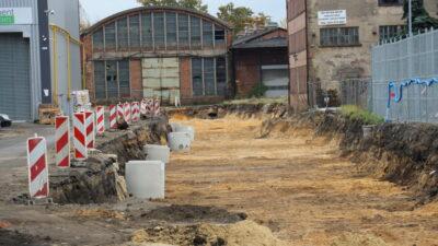 prace przy budowie drogi przez Dozamet - wykopany dół w tle dawne hale zakładu