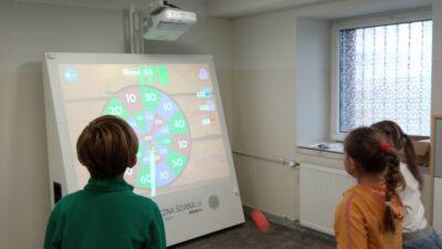 dzieci przed multimedialną tablicą w w sali doświadczeń świata