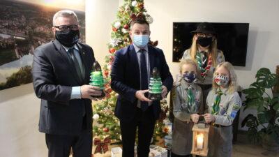 od lewej prezydent Jacek Milewski, przewodniczący rady miejskiej Andrzej Petreczko oraz trzy harcerki nowosolskiego hufca ZHP. Wszyscy mają w dłoniach lampiony ze światełkiem betlejemskim, w tle choinka świąteczna