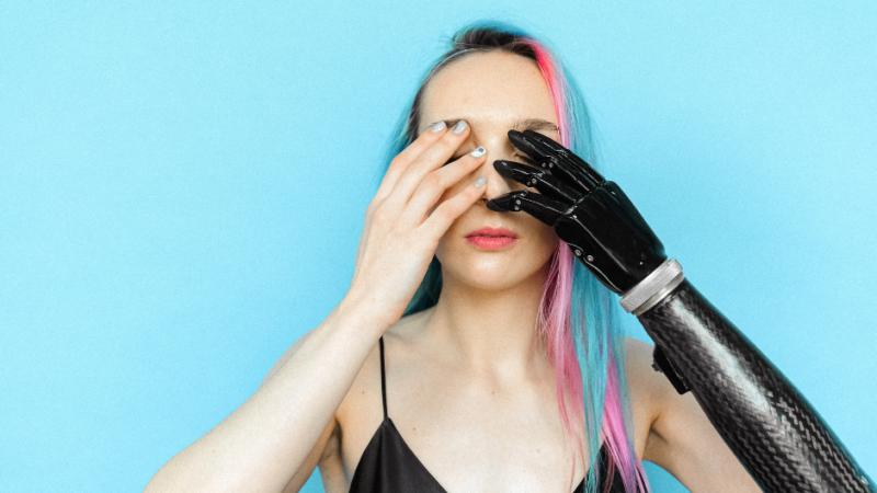 Kobieta zasłania rękoma oczy, jedna z jej rąk to proteza w czarnym kolorze.
