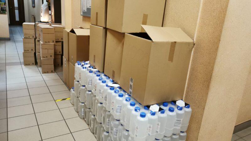 pudła z maseczkami ochronnymi i płynami do dezynfekcji dłoni. stoją na korytarzu urzędu