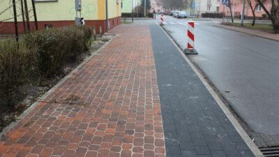 budowa chodników przy ulicy Wesołej w Nowej Soli. Nowa nawierzchnia chodników składająca się z dwóch kolorów kostki brukowej czerwony i grafit, wzdłuż ulicy rozstawione słupki bezpieczeństwa