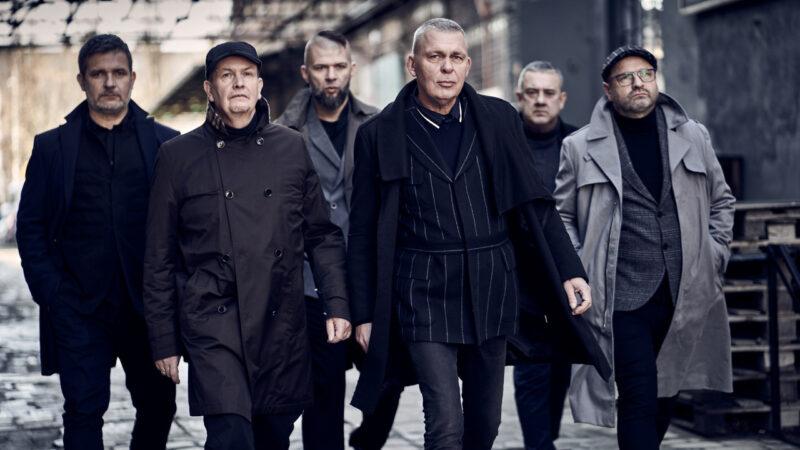 zdjęcie zespołu Raz Dwa Trzy. Sześciu mężczyzn w płaszczach, idą w budynku pofabrycznej hali