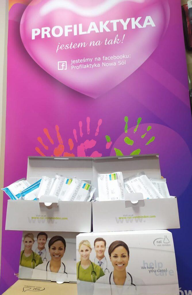 na tle różowego rolapa z logo z napisem Profilaktyka jestem na tak, widnieją kartoniki z testami na wykrywanie obecności narkotyków w organizmie.