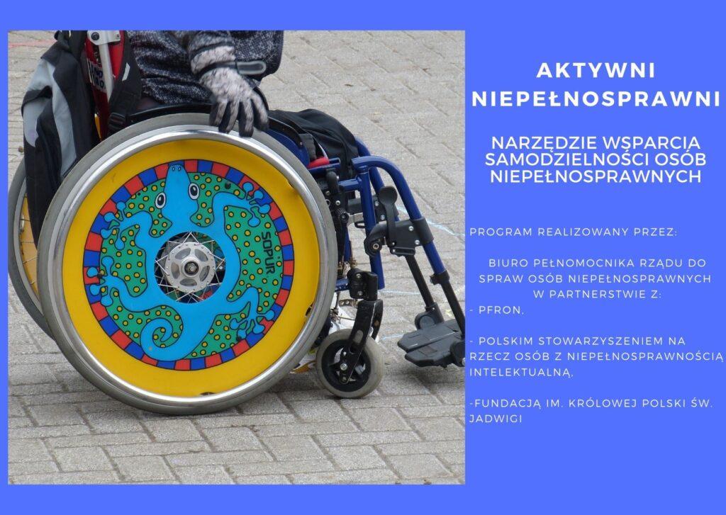 grafika przedstawia zdjęcie osoby siedzącej na wózku inwalidzkim, którego koła są pomalowane we wzór kolorowej mandali