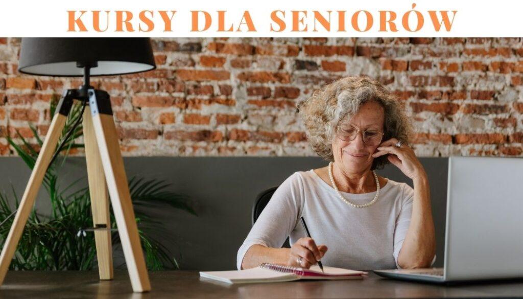 Na zdjęciu widoczna seniorka, która siedzi przed laptopem, w jednej ręce trzyma długopis i notuje w zeszycie.