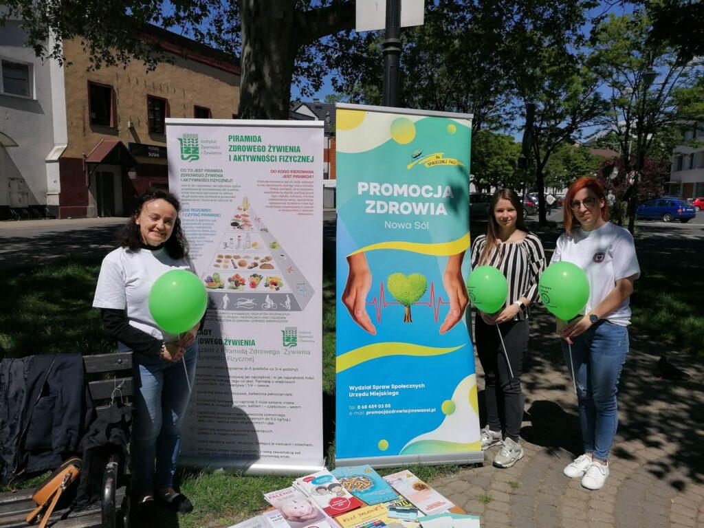 Na zdjęciu widać 3 kobiety, które stoją na tle dwóch rollupów, w dłoniach trzymają zielone balony z okazji światowego dnia bez tytoniu. Zdjęcie wykonane na dworze, na skwerze.
