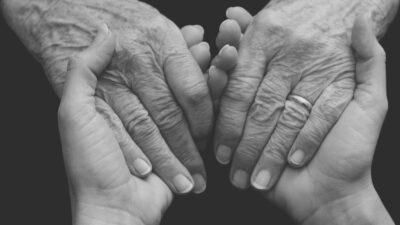 dwie dłonie starszej osoby, dwie dłonie młodej osoby - splecione w uścisku
