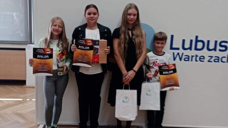 czworo dzieci trzy dziewczynki i chłopiec prezentują dyplomy i nagrody które otrzymały w konkursie