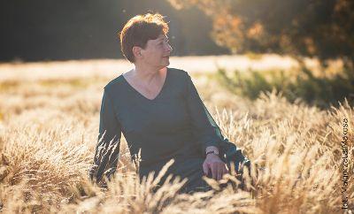 Na zdjęciu pisarka Zofia Mąkosa która siedzi na trawie. Jest słoneczna, jesienna pogoda