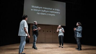 Na zdjęciu czworo aktorów Teatru Polska podczas spektaklu pod tytułem Jeden Gest. Stoją w kręgu i komunikują się za pomocą gestów. W tle ekran wyświetlający tekst ich rozmowy