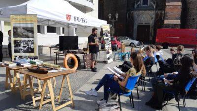 Animator Fundacji Otwartego Muzeum Techniki stoi przed mlodymi ludźmi, którzy z zaciekawieniem słuchają wykładu na temat żeglugi śródlądowej. W tle namiot wystawienniczy.
