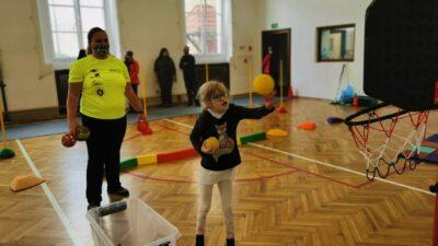uczestnicy olimpiady radość podczas zawodów sportowych - dziewczynka stara się wrzucić piłeczki do zawieszonego kosza