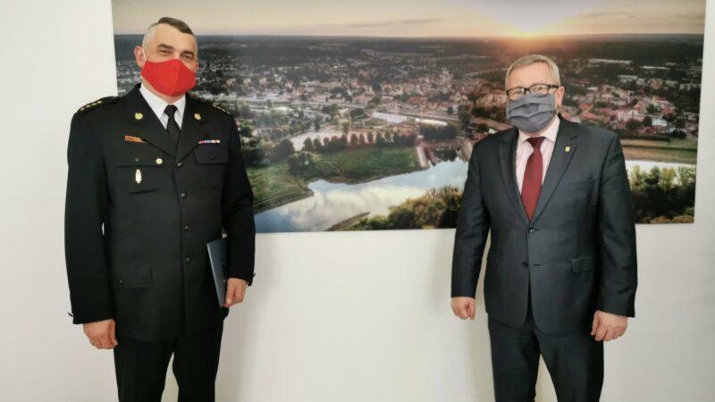 Na zdjęciu od lewej komendant Tomasz Duber oraz prezydent Jacek Milewski. Panowie stoją w dystansie od siebie na twarzy mają maseczki zasłaniające usta i nos