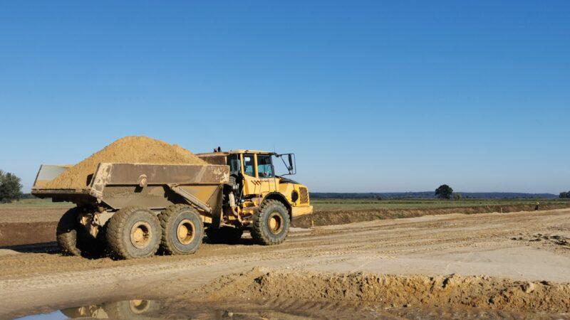 Na zdjęciu widzimy zakres prac związanych z inwestycją pod nazwą Ochrona przeciwpowodziowa miasta Nowa Sól i obszarów poniżej miasta Krosno Odrzańskie - na zdjęciu znajdują się wytyczone szerokie pasy ziemi pod budowę wałów. w tle ciężarówka z piachem